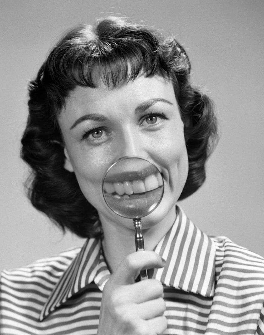 1950s smiling portrait brunette woman looking at camera holding magnifying glass to mouth